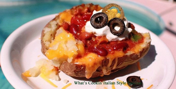 this is a chili topped baked potatoes loaded with shredded cheeses, olives, sour cream and chopped tomatoes