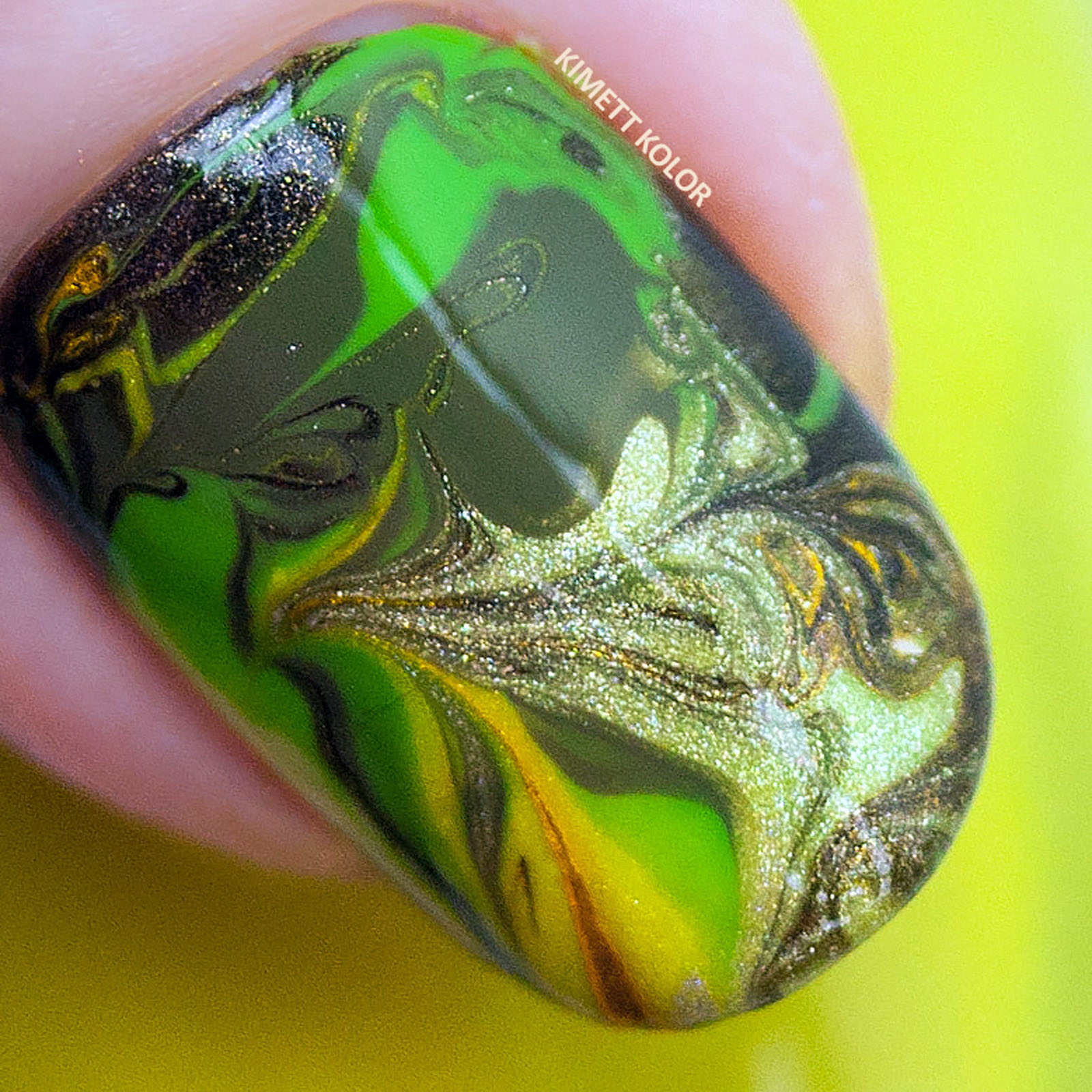 Macro of drag marble nail art in green gold and brown