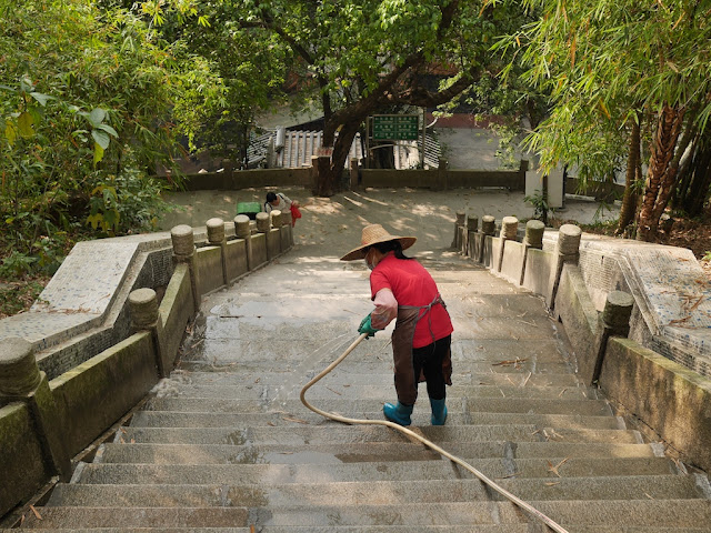 woman spraying water from a hose onto stone steps