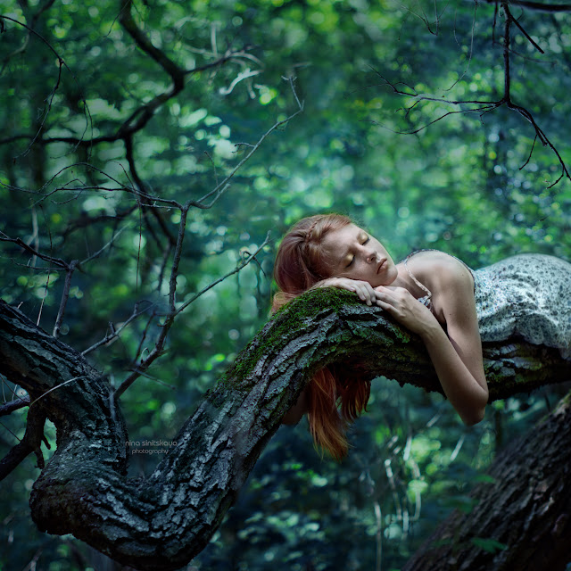 Girl with red hair and freckles sleeps on the branch of tree covered with moss