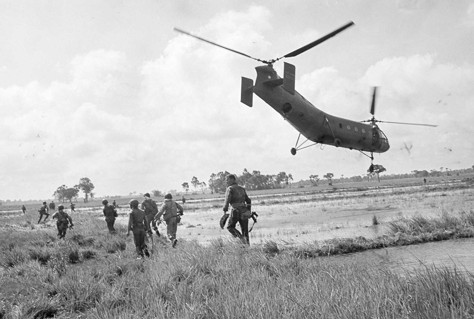 Vietnamese airborne rangers, their two U.S. advisers, and a team of 12 U.S. Special Forces troops set out to raid a Viet Cong supply base 62 miles northwest of Saigon, on August 6, 1963. As the H-21 helicopters hovered six feet from the ground to avoid spikes and wires and under sniper fire, the troops jumped out to attack.