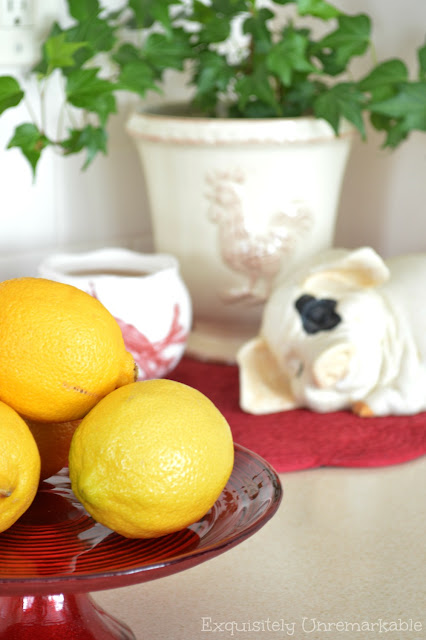 Lemons on a red plate rack with a pig statue in the background