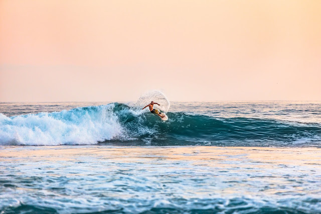 surfer riding in the sunset