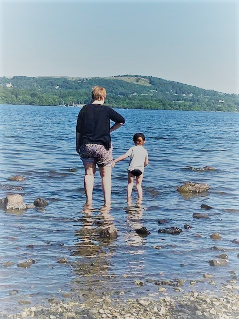 Little boy and mum paddling in the lake