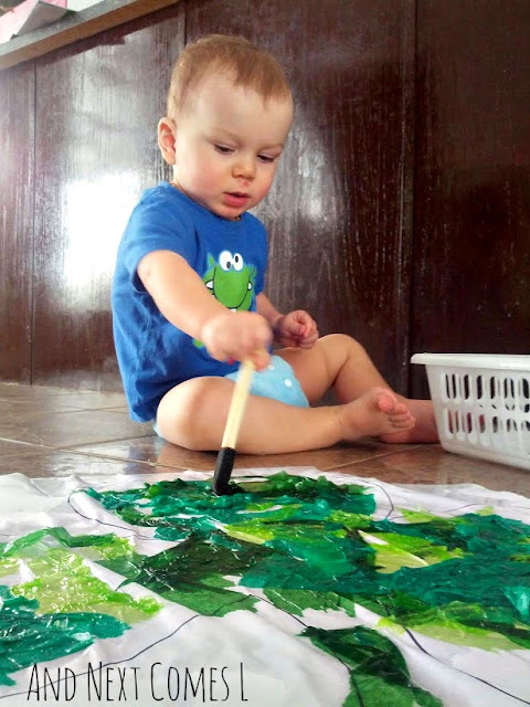Toddler doing bleeding tissue paper art project for St. Patrick's Day