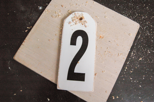 Drilled hole in top of distressed number tags