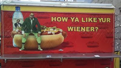 "Man sitting on giant hot dog. Caption: ""How ya like yur wiener?"""