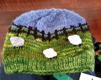 A knitted beanie with a ribbed cuff and rounded top, using short rows to shape the top. The beanie is a pastoral scene. The bottom half is green with variegated yellow, white and earthy orange brown to represent the pasture. A fair isle  pattern in brown alternating with green and brown and then alternating with blue and brown depicts a fenceline. The blue top depicts the sky.  White knitted sheep are appliqued onto the 'grass' and the sheep's feet and faces are embroidered in black yarn.