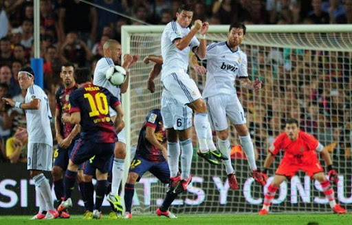 Barcelona player Lionel Messi takes a free-kick to score a goal against Real Madrid