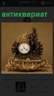 Старинные часы на подставке, обрамленные красивыми вензелями по бокам