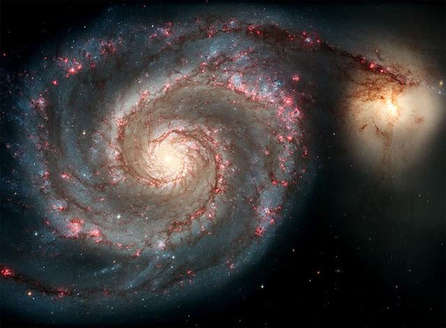 Colisão entre a galáxia M51a - conhecida como A Galáxia do Rodamoinho - e a galáxia M51b