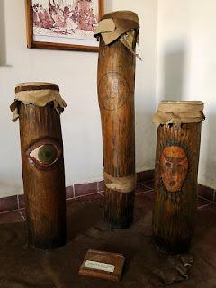Kuba, Matanzas, Museo de la Ruta de los Escalavos mit Castillo de San Severino, hohe, baummstammförmige Ritualtrommeln aus Holz, bemalt mit Auge und Masken.