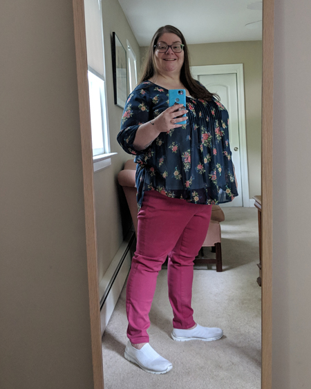 image of me standing in a full-length mirror, with my hair down, wearing grey-framed glasses, a blue blouse with a floral pattern, pink jeans, and white sneakers