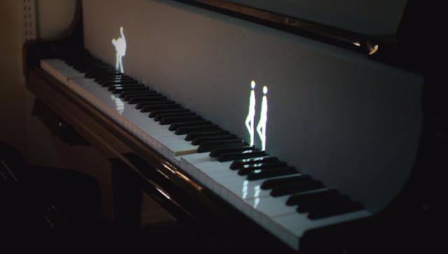 Figuras luminosas tocan el piano con sus pasos de baile