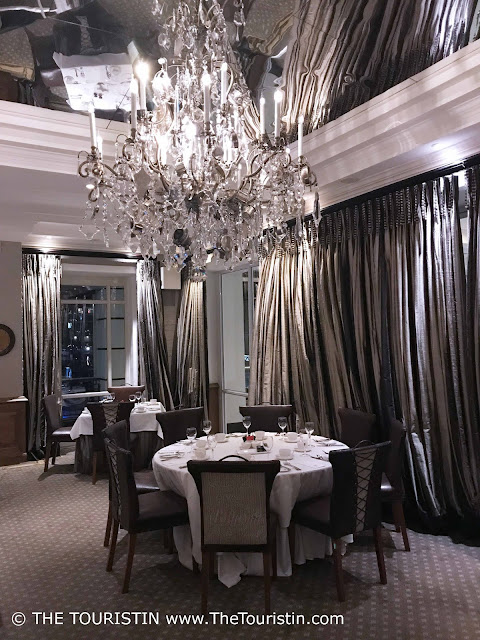 Tables set with white table clothes and silver cuttlery under a large glass chandelier.