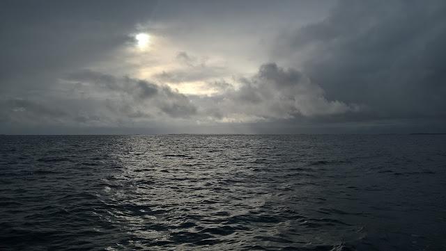 Tumma meri, pilvinen taivas. Pilvien takaa siilautuu auringon valoa.