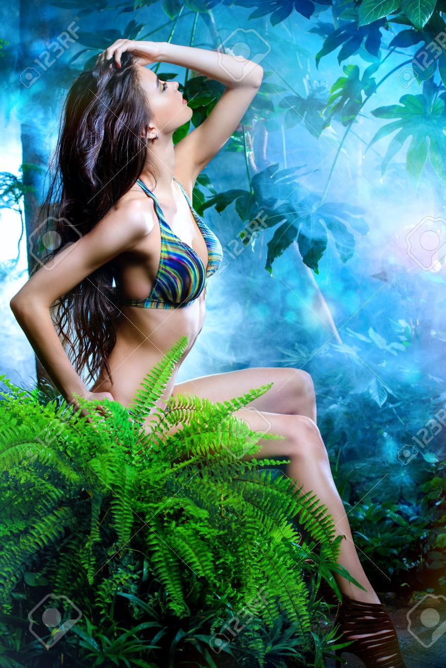 Beautiful sexy woman in bikini among tropical plants