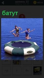 Надувной батут плавает на воде, на котором прыгаю две девушки поджав ноги и раскинув руки в стороны