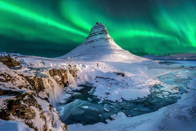 Kirkjufell mountain covered in snow and with the Northern Lights dancing in the background