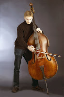 Ayakta kontrbas çalgısı çalan bir genç adam