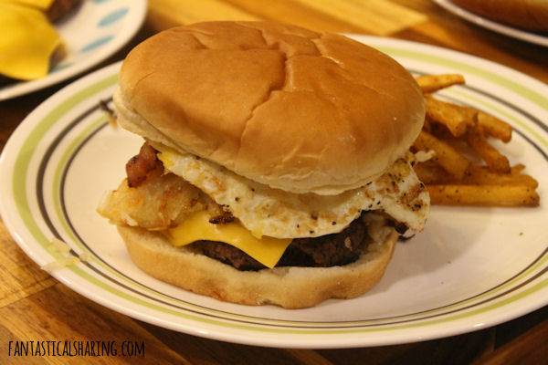 Copycat Applebee's All-In Brunch Burgers // This burger is stacked with bacon, fried egg, and hashbrown - it's breakfast on a bun! #recipe #copycat #FantasticalFoodFight #beef #burger #applebees