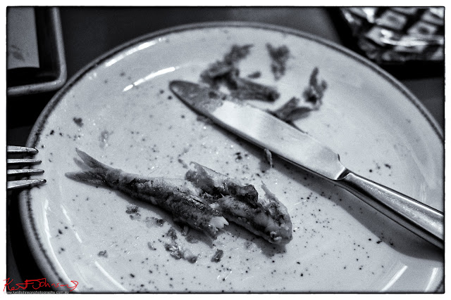 Sardines on the plate, knife and fork, at Trattoria Da Oscar.  Photograph by Kent Johnson