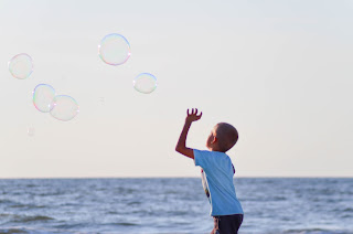 Chld playing with bubbles in the sea shore