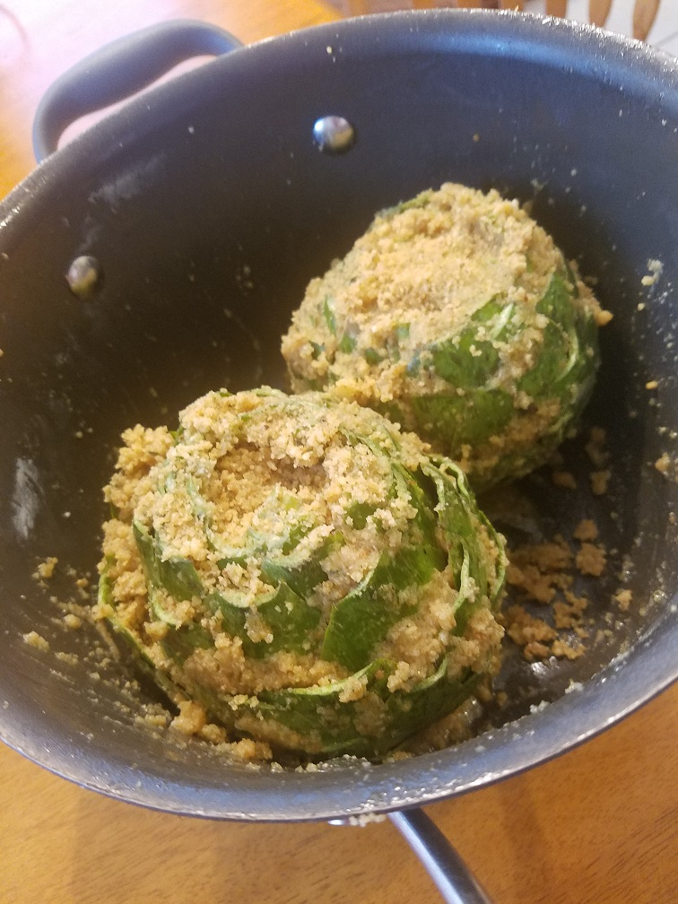 These are stuffed Italian artichokes with bread crumb and spices in a pan ready to slow simmer under tender
