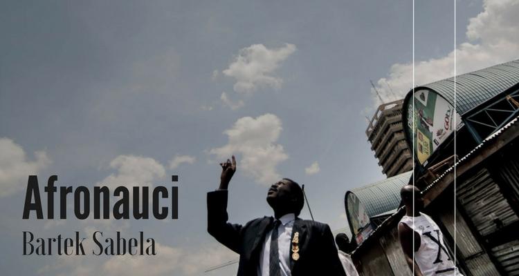 Czarnoskóry mężczyzna w garniturze z przypiętymi odznaczeniami wskazuje palcem w błękitne niebo.