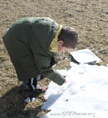 Boy collecting snow sample in order to test pH: STEMmom.org