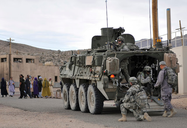 Soldiers from U.S. Army Alpha Company, 2-3 Inf, 3-2 SBCT, patrol a village with Afghan forces at the National Training Center in Fort Irwin, California, U.S. on August 13, 2011.   Courtesy Ryan Hallock/U.S. Army/Handout via REUTERS
