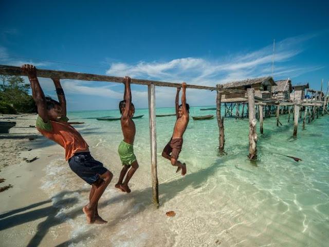 Ng Choo Kia - Crianças Bajau brincam em ponte simples feita de uma unica taboa sobre o mar