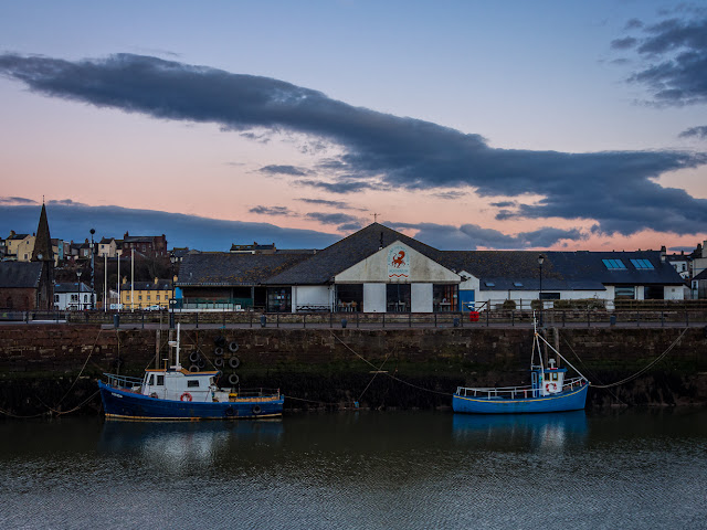 Photo of The Aquarium from across Maryport harbour at sunset