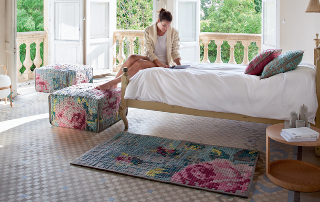Woman releaxing in bedroom with chunky cross stitch rug and foot stools