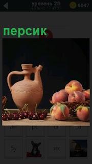 На столе стоит кувшин и рядом находится корзина с персиками внутри, так же лежит вишня