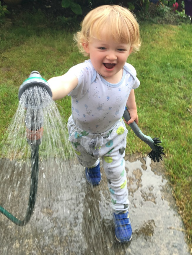 An-Indian-Summer-image-of-toddler-with-hose-pipe