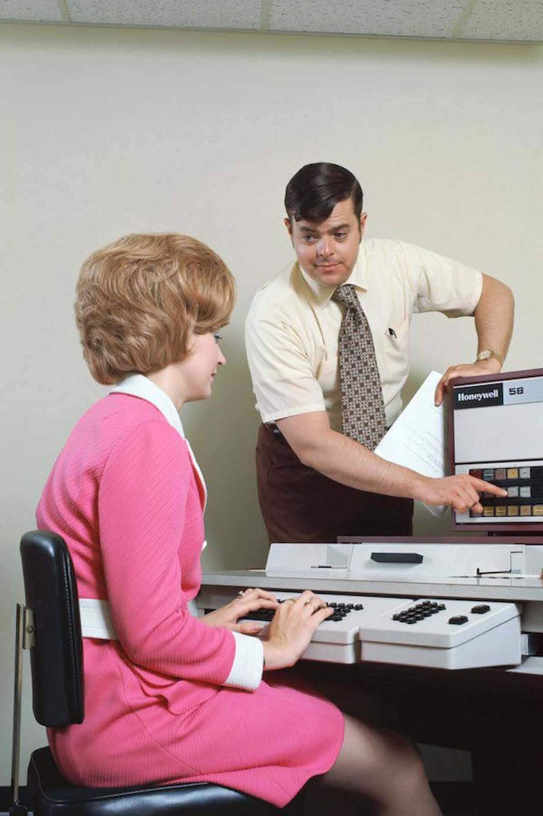A woman using a data entry computer. She wears a bright pink skirt suit with white collar, cuffs and belt. The skirt is between thigh- and knee-length. Her hair is highly stylised, likely held in place with hairspray. 1970s.