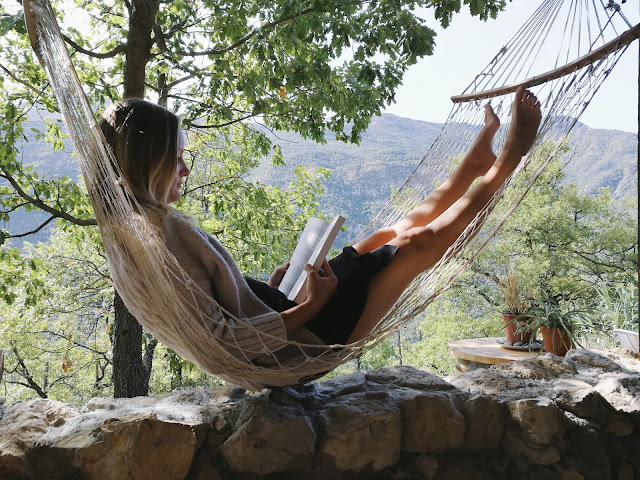 Mama lying in a hammock reading a book