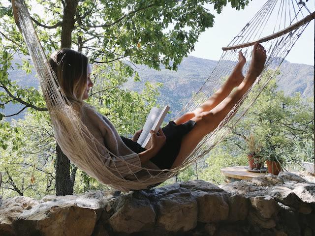 Mama lying in a hammock reading a book