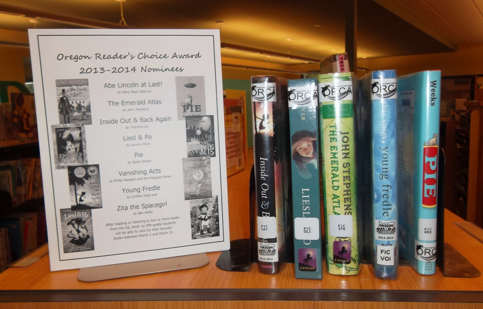 A poster held up by a bookend displays cover art and lists titles and authors for ORCA upper-elementary division nominees: Abe Lincoln at Last! by Mary Pope Osborne, The Emerald Atlas by John Stephens, Inside Out & Back Again by Thanhha Lai, Liesl & Po by Lauren Oliver, Pie by Sarah Weeks, Vanishing Acts by Phillip Margolin and Ami Margolin Rome, Young Fredle by Cynthia Voigt and Zita the Spacegirl by Ben Hatke. To the poster's right, five books -- Inside Out & Back Again, Liesl & Po, The Emerald Atlas, Young Fredle and Pie -- are shelved between bookends. Each book has an ORCA label on its spine.