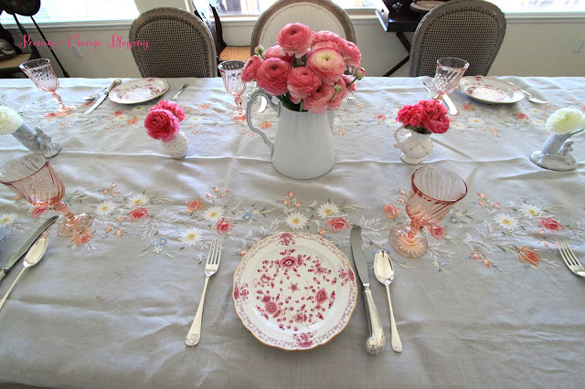 Spring French table setting with Madeira table cloth, Meissen plates, pink and white ranunculus, and vintage French goblets.