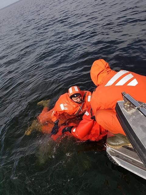 Yksi henkilö veneessä auttaa kahta pelastautumispukuista veneeseen