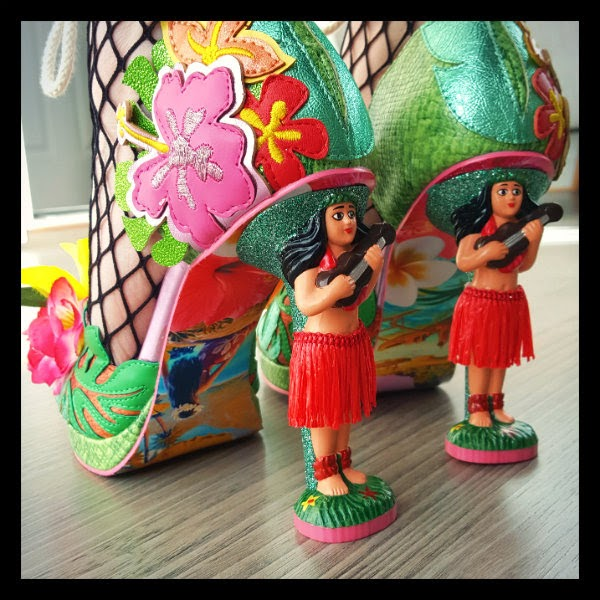 back view detail of two feet wearing hula girl heeled shoes with pretty Hawaii patterned soles visible