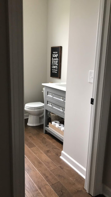 Powder room with wood floors gray vanity