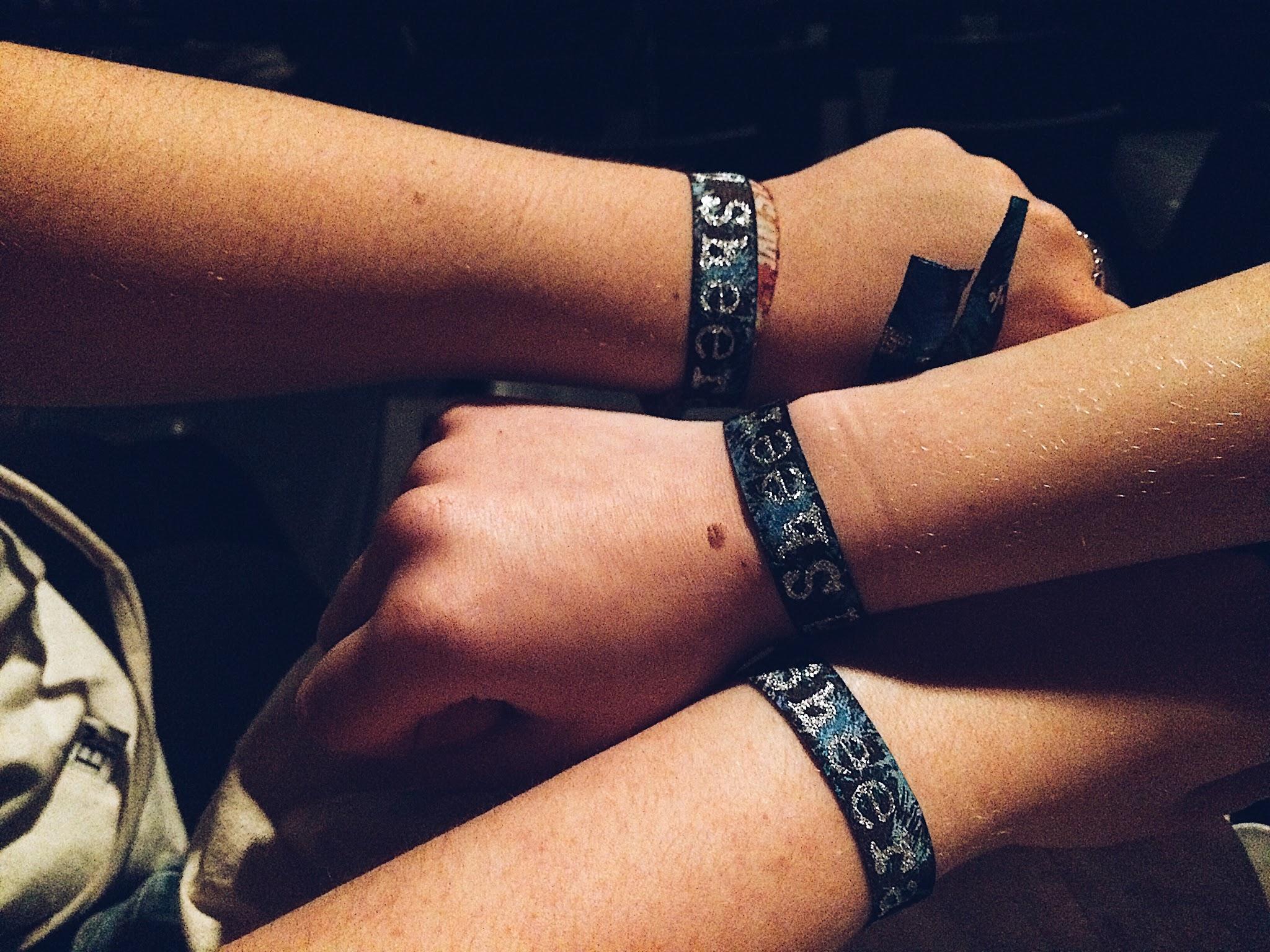 Drie meisjes met het concertbandje van Ed Sheeran aan hun arm.