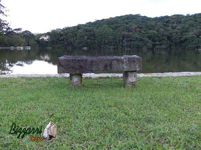 Banco de pedra com pedra folheta em frente ao lago com os muros de pedra.