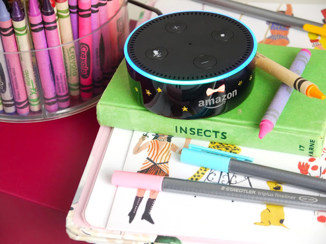 a black amazon echo dot sat on a green book with colourful crayons and fineliner pens around it