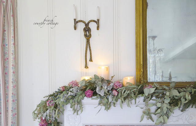 Garland on mantel with flowers and gold mirror