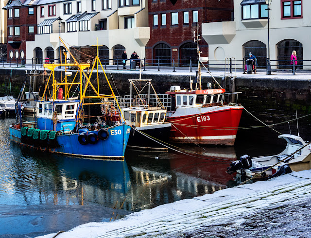 Photo of colourful fishing boats in Maryport Harbour with a dusting of snow