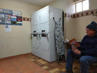 Man reading a book at a laundromat